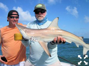 Jeff Stresing (left), from Parrish, FL, and Capt. Rick Grassett with a blacktip shark that Jeff caught and released on a threadfin while fishing the coastal gulf with Capt. Rick Grassett.