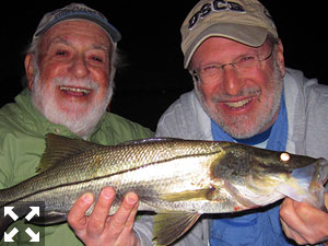 Martin Marlowe, from NY, and his son Bruce Marlowe, from SC, with a couple of snook caught and released on a Grassett Snook Minnow fly while fishing the ICW at night with Capt. Rick Grassett.