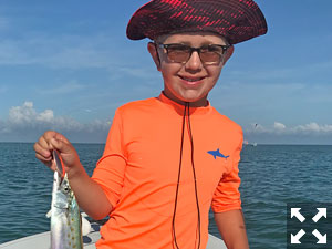 Kellen, looking a bit like a modern day brightly colored pirate, holds one of his  many mackerel that he caught.